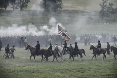 Bringing the flag forward. Cavalry and foot soldiers on the battlefield at the 150th anniversary of the battle of Gettysburg, Pennsylvania Stock Image