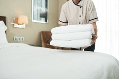 Bringing fresh towels. Cropped image of maid bringing stack of fresh fluffy towels royalty free stock images