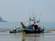 Fishing boat being launched in surf Stock Photo