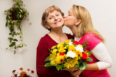 Bringing joy to somebody. Daughter giving her mother a bouquet Royalty Free Stock Photos