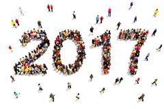 Bringing in the new year. Large group of people in the shape of 2017 celebrating a new year , or future goals and growth concept o Stock Photos