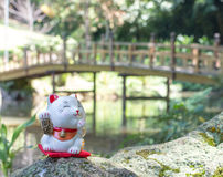It brings good fortune and luck, Maneki Neko Cat. Statue of a Maneki Neko outside, near lake and woodden bridge royalty free stock photos