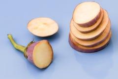 Brinjal茄子切在被隔绝的蓝色背景的片断 免版税库存图片