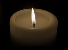 Brinna stearinljus på en svart bakgrund Arkivbild
