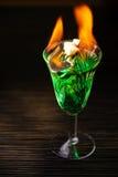 Brinnande absint på mörk tabellbakgrund Royaltyfria Bilder