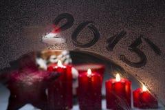 Brinnande adventstearinljus på det frostade fönstret med ny year 2015 Royaltyfria Bilder