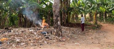 Brinnande avskräde för folk, man som håller ögonen på, zanzibar Arkivbild