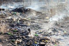 Brinnande avskräde på den olagliga förlorade dumoen nära skogsvartjord och tungt skräp röker Miljöbelastningefterdyningbegrepp royaltyfria foton