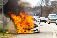 Brinnande bil på brand på en huvudvägvägolycka Royaltyfri Bild