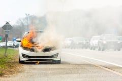 Brinnande bil på brand på en huvudvägvägolycka Arkivfoto