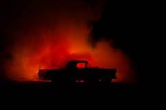 Brinnande bil på en mörk bakgrund Bil som fångar brand, efter handling av den indicent vandalism eller vägen Arkivbilder