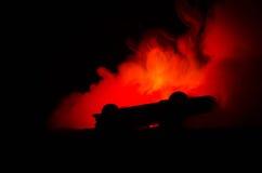 Brinnande bil på en mörk bakgrund Bil som fångar brand, efter handling av den indicent vandalism eller vägen Arkivbild