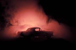 Brinnande bil på en mörk bakgrund Bil som fångar brand, efter handling av den indicent vandalism eller vägen Royaltyfri Foto