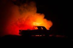 Brinnande bil på en mörk bakgrund Bil som fångar brand, efter handling av den indicent vandalism eller vägen Royaltyfri Bild