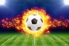 Brinnande fotbollboll ovanför grön fotbollsarena Arkivbilder