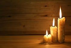 Brinnande gammal stearinljus på trätappningbakgrund Royaltyfri Foto