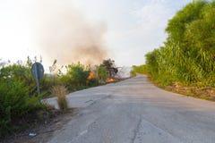 Brinnande gräs och svart moln arkivfoto