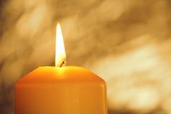 Brinnande guld- stearinljus Fotografering för Bildbyråer