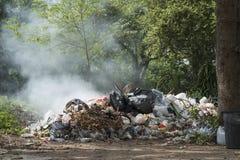 Brinnande hög av avskräde, orsak av luftförorening royaltyfri foto