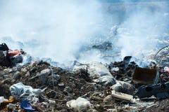 Brinnande hög av avskräde, orsak av luftförorening Oljetrumma och världsöversikt rubbish royaltyfri foto