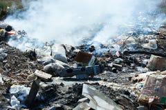 Brinnande hög av avskräde, orsak av luftförorening Oljetrumma och världsöversikt rubbish royaltyfri fotografi