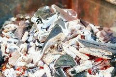 Brinnande kol med den orangefärgade flamman och den selektiva fokusen för glöd, på delar av styckena runt om Arkivfoto