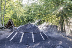 Brinnande kolhög i skogen Arkivfoto