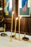 Brinnande kyrkastearinljus i de kyrkliga inre Royaltyfri Bild
