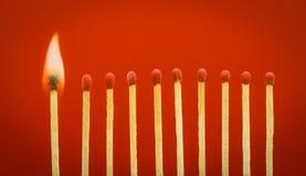 Brinnande matchsticks som ställer in brand till dess grannar Royaltyfri Foto