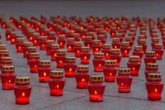 Brinnande minnesmärkestearinljus i röda lyktor på granittjock skiva arkivbilder