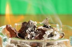 Brinnande papper i ett glass askfat Arkivbild