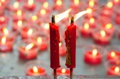 Brinnande röd stearinljus på den kinesiska relikskrin för framställning av merit i kines Arkivbilder