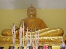Brinnande rökelse klibbar framme av en guld- Buddhastaty med vinkande röka Royaltyfri Fotografi