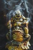 Brinnande rökelse klibbar med guld- Buddha på paddan Royaltyfri Foto