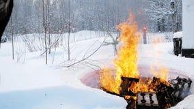 Brinnande saker i natur i vinter gem Mannen bränner gammal saker i skogbegreppet av att sära med forntiden arkivfilmer