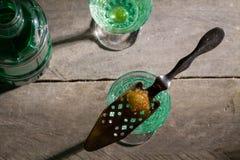 Brinnande socker på skeden i exponeringsglas av absint royaltyfri foto