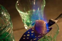 Brinnande socker på skeden i exponeringsglas av absint Royaltyfri Fotografi
