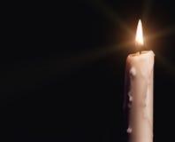 Brinnande stearinljus över svart Arkivfoto