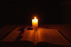 Brinnande stearinljus, bibel och kors på skrivbordet Arkivbild
