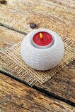Brinnande stearinljus i en ljusstake på en träbakgrund Fotografering för Bildbyråer