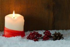 Brinnande stearinljus i snö arkivfoto