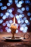 Brinnande stearinljus i tappningmässingsljusstakeanseendet på gammalt trä Royaltyfria Foton