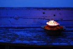 Brinnande stearinljus och blommor Närbild hinduism arkivfoton