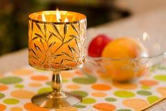 Brinnande stearinljus- och fruktplatta Arkivbilder