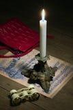 Brinnande stearinljus, operaexponeringsglas och en liten handväska arkivfoton