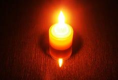Brinnande stearinljus på en reflekterande tabell Synlig stearinljus och dess referens Royaltyfri Bild