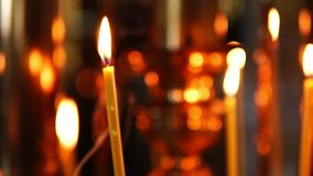 Brinnande stearinljuscloseup på bakgrunden av andra stearinljus i Christian Orthodox Church lager videofilmer