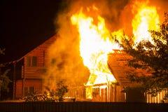 Brinnande trähus på natten Ljusa apelsinflammor och tät sm royaltyfri fotografi