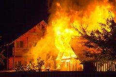Brinnande trähus på natten Ljusa apelsinflammor och tät sm royaltyfri foto