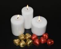 Brinnande vitstearinljus och godis på en svart bakgrund Royaltyfri Fotografi